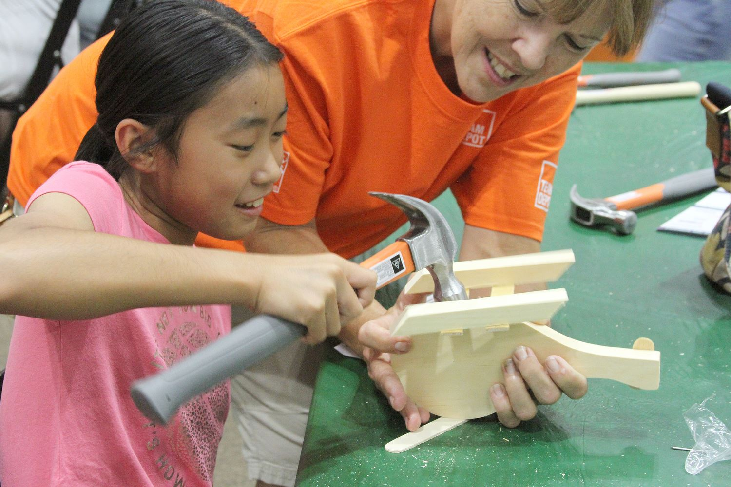 Little girl with a Home Depot volunteer hammering her wood craft