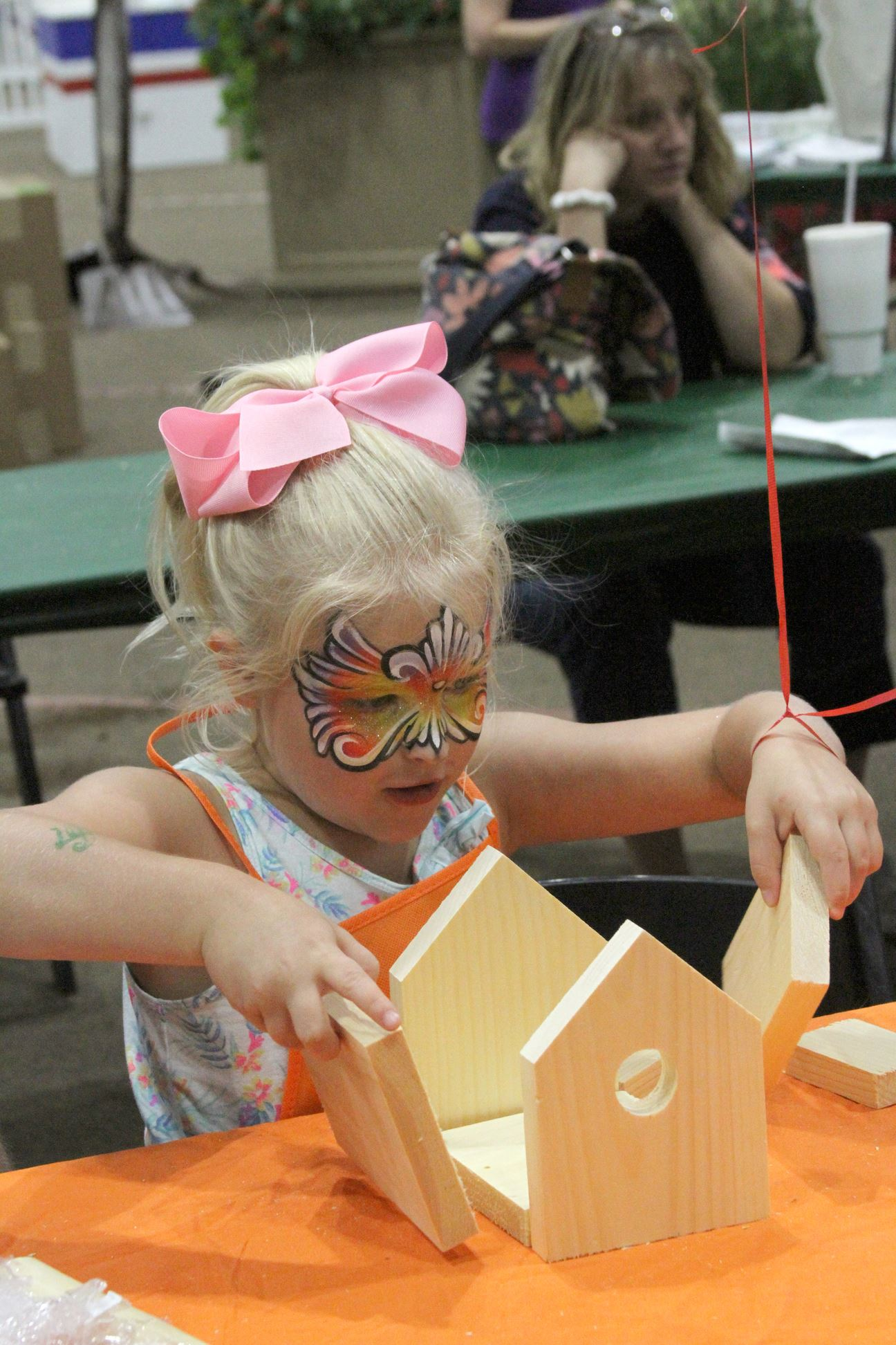 Little girl with her face painted with a butterfly putting together a birdhouse