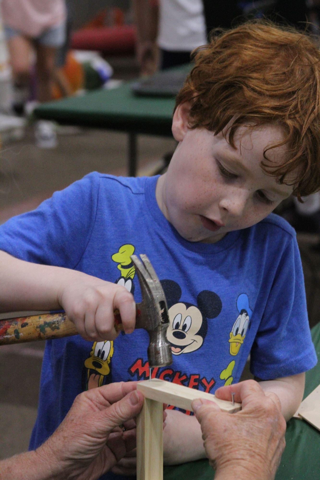 A little boy hammering wood