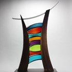 Abstract, sculptural designs in metal with rich patina finishes and colored blown glass