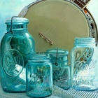blue glass jars in front of a banjo