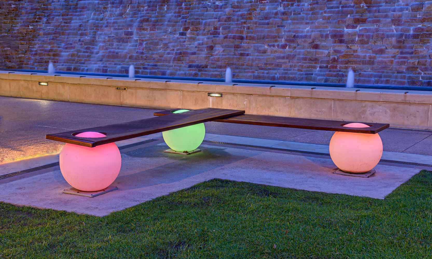 Bench with neon glowing balls holding wooden planks as seating
