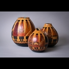 Gourd wood-burned and dyed with inlaid stones and linen-laced opening