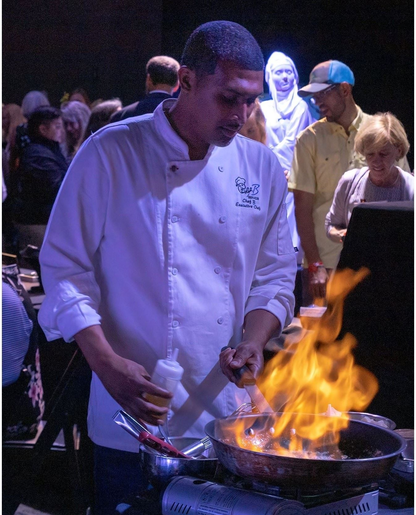 Man in chef coat cooking with flames coming from a pan