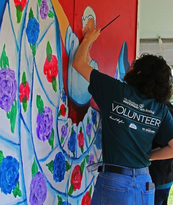 Girl wearing volunteer shirt painting a big picture